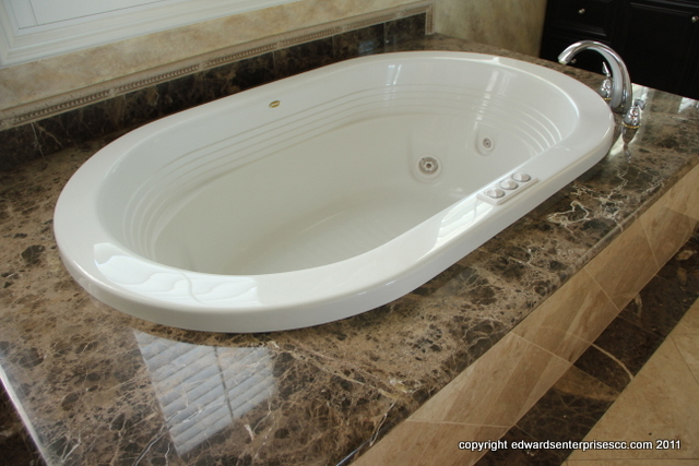 Bathtub With Roman Tub Faucet In Master Bathroom Suite Surrounded By  Granite Deck
