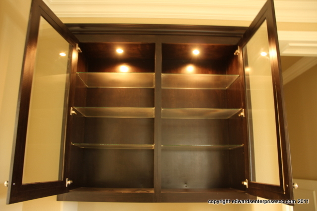 Under Cabinet lighting work in a Santa Barbara residential cabinet with glass shelves. Your home can look like this too! Edward's Enterprises Cabinet Lighting.