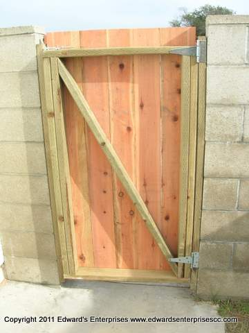 Pedestrian side gate constructed of pressure treated 2X4s & flat top redwood 6 inch pickets attached to block wall