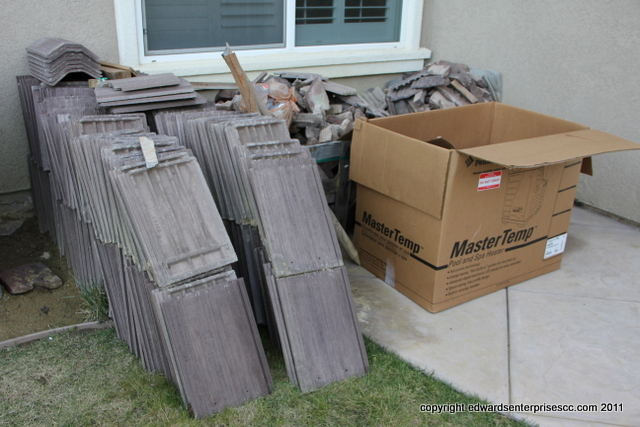 Stack of left over building materials like roofing tiles ready to be picked up & hauled away to a proper landfill