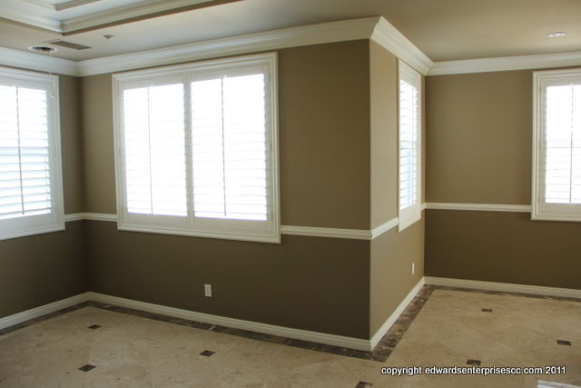 A master bedroom suite with base, chair & crown moulding repainted in a 2 tone brown scheme with white trim