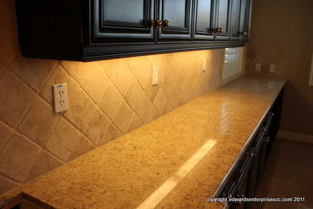 Beautiful granite countertop in a residential customer's home highlighted by under cabinet fluorescent lighting: Edward's Enterprises Santa Barbara Cabinet Lighting.