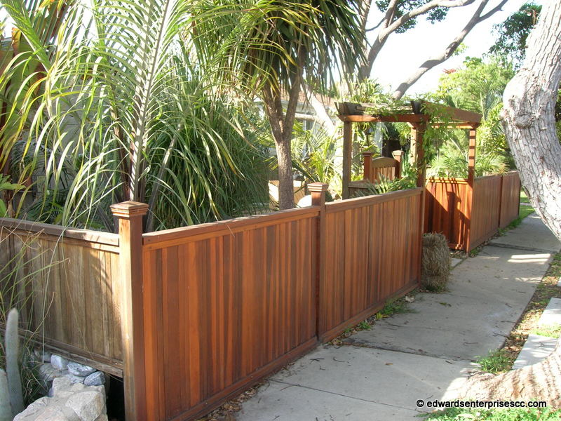 home front yard fence & gate design inspiration with a trellis over walkway & a 3 foot stained fence along sidewalk.
