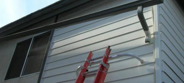 Ladder on the side of a house reaching up toward a damaged rain gutter