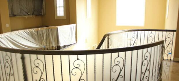Circular stairway railing, draped in translucent plastic