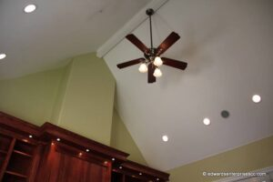 Ceiling fan with three lights at the peak of a vaulted ceiling with recessed lights to the side