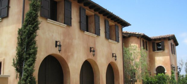 Front of two story Spanish-style home with smooth stucco finish