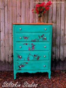 Dresser painted aqua, distressed and flowers painted on the front