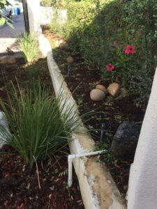 Stucco retaining wall in garden with sprinkler system