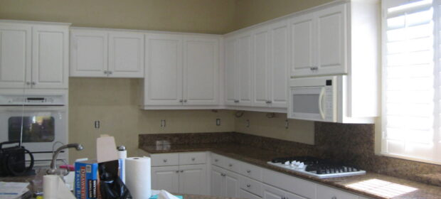 Kitchen with white cabinets being remodeled, after wallpaper removed