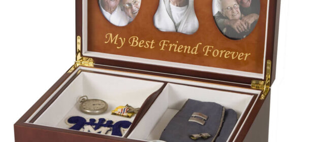 """Wooden box with photos of elderly man under lid and the text """"My best friend""""; Inside: a military garrison cap, watch, medal, and patch"""