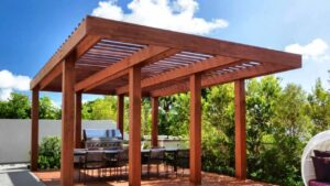 Wooden pergola over an outdoor table and barbecue grill