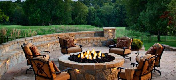 Patio with six soft seat chairs surrounding a fire pit