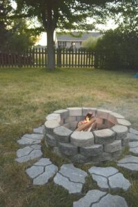 Stone fire pit on lawn surrounded by pavers