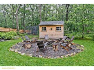 Rustically styled, six chairs surrounding fire pit on gravel circle in the middle of lawn