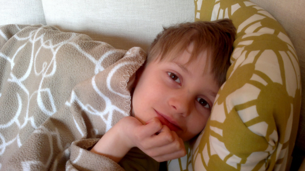 Child lying on couch under blanket smiling at camera