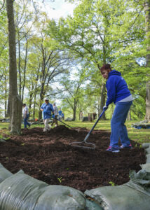Peope spreading compost on the ground