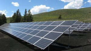 Solar panels with a grassy hill in the background