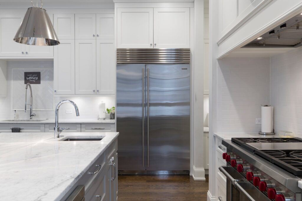 Stainless steel refrigerator in modern, white kitchen