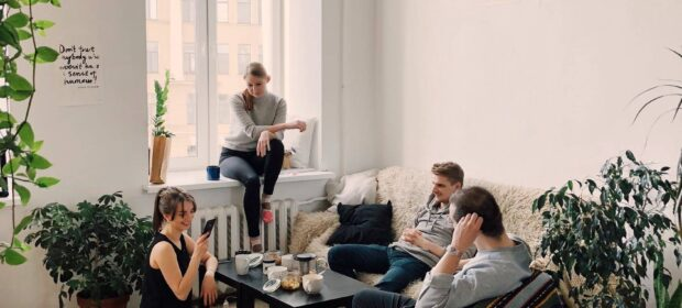 Four people in living room with shag rug