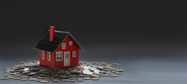 Tiny house on a pile of coins