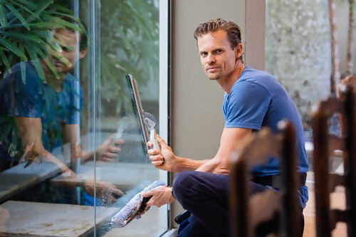 Man cleaning window from inside home