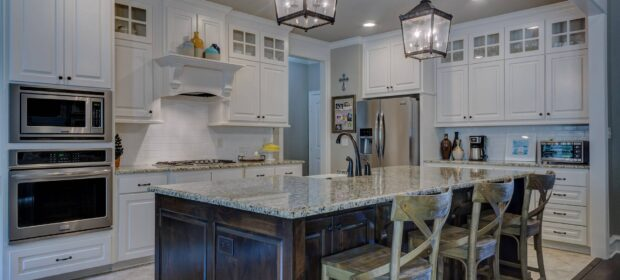White kitchen with island and marble countertops