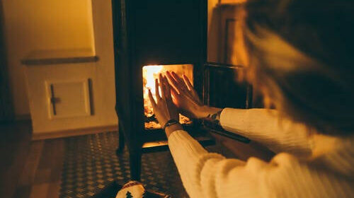 Woman warming hands by wood burning heater