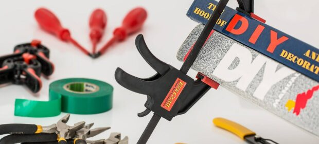 Clamp holding DIY books, pliers, and other tools on a white field