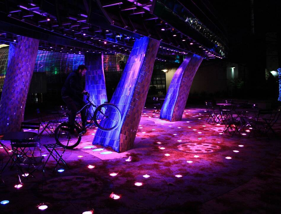 Outdoor purple-pink LED lighting, with man standing with a BMX bike