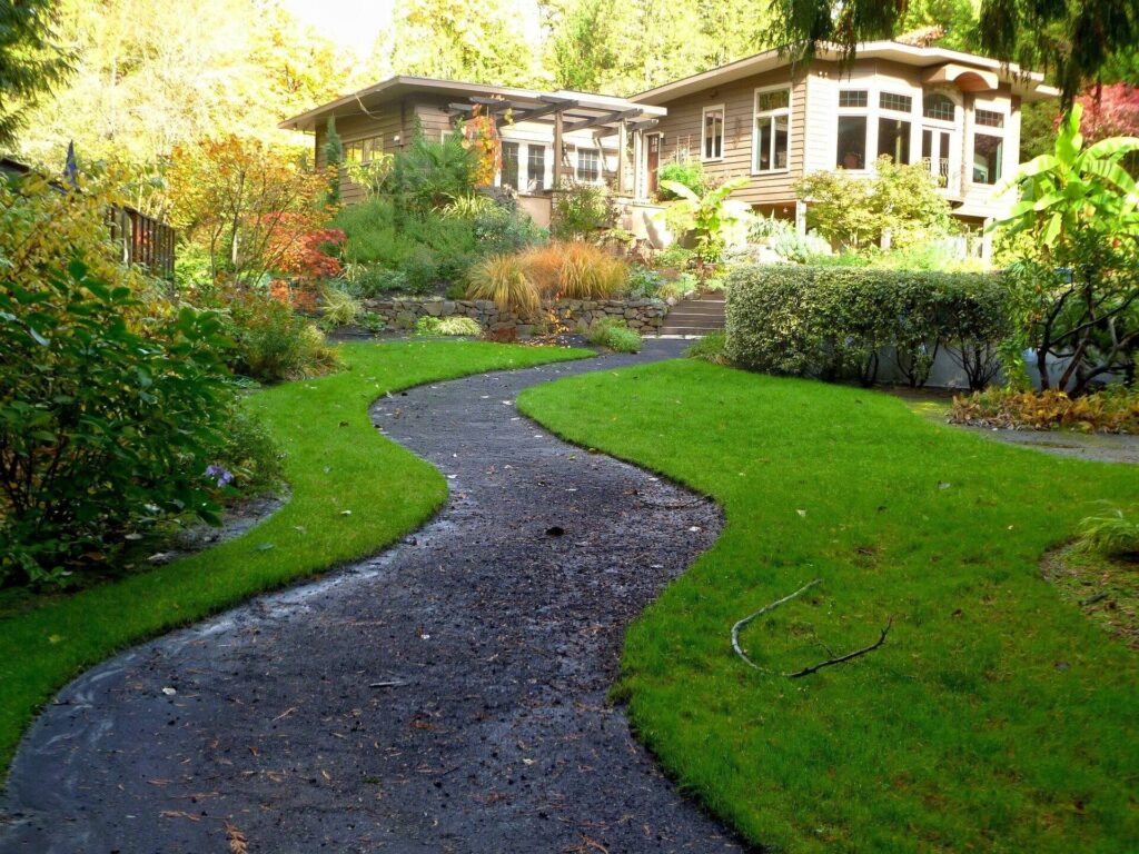 Nice little fancy/rustic house with path leading to it with lawn and garden on both sides