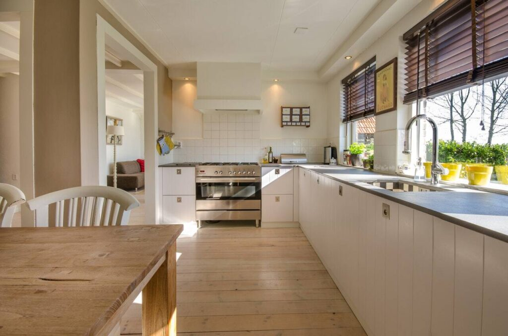 Kitchen with white oak floor, white cabinetry and walls, and light coming through the window