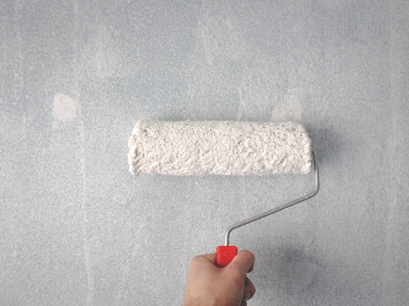 paint roller with white paint about to paint the wall